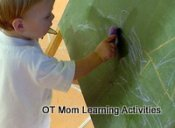 toddler scribbling on blackboard