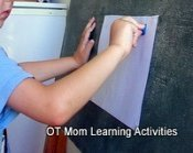 child using rubber stamps on a vertical surface