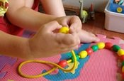 child threading beads